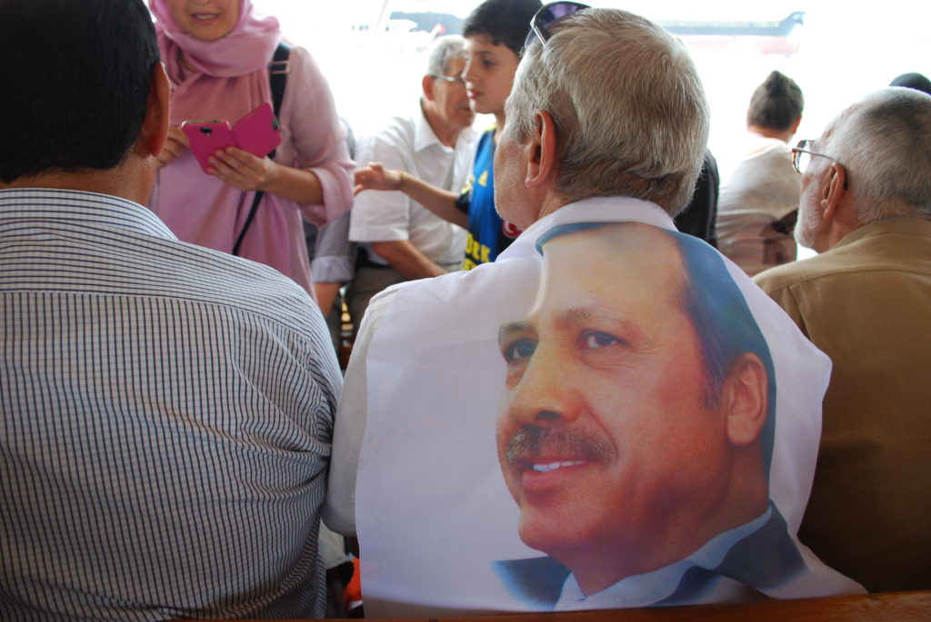 A supporter of the AKP drapes a photo of Erdoğan over his shoulders. Photo: Jenna Krajeski.