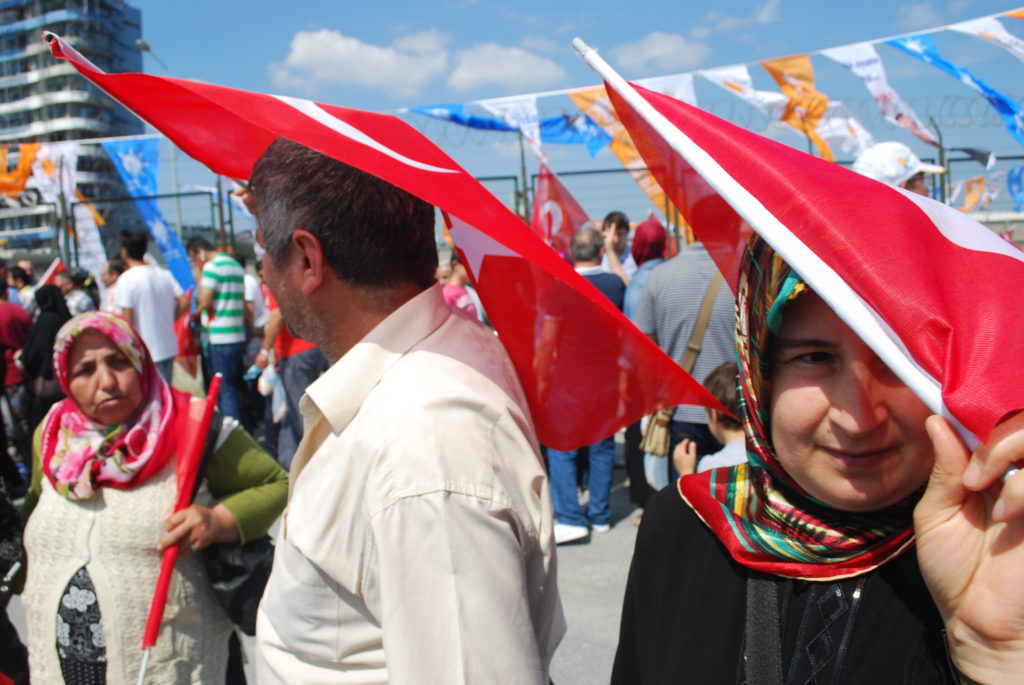 Supporters of Prime Minister Recep Tayyip Erdogan shield themselves from the midday sun with Turkish flags on their way to a rally in support of Erdoğan and the AKP. Photo: Jenna Krajeski.